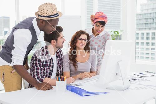 Smiling coworkers using computer monitor