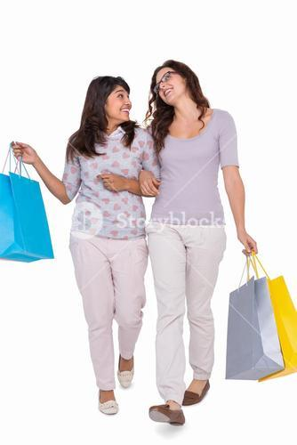 Smiling friends walking with shopping bags