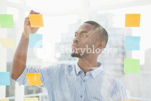 Thoughtful businessman writing on sticky notes on window