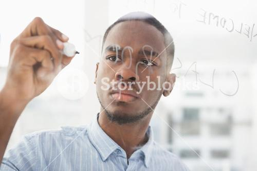 Focused businessman writing on clear board