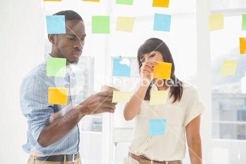 Concentrated coworkers looking at sticky notes