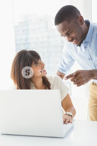 Happy coworkers using laptop together