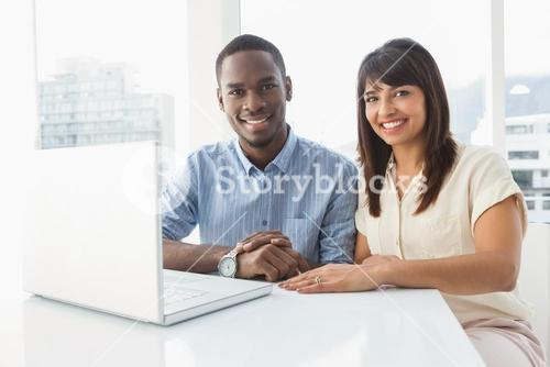 Happy casual coworkers using laptop