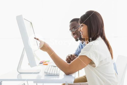 Cheerful teamwork using computer monitor