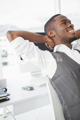 Relaxed businessman with hands behind head
