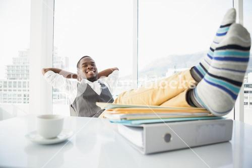 Relaxed businessman sitting in his chair with feet up
