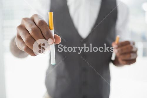 Businessman holding electronic cigarette and cigarette
