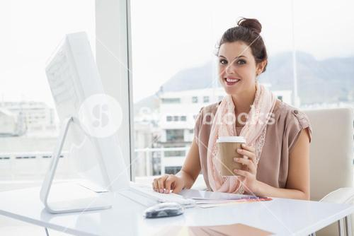 Smiling businesswoman holding paper cup of coffee