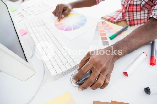 Businessman pointing colour wheel and using mouse