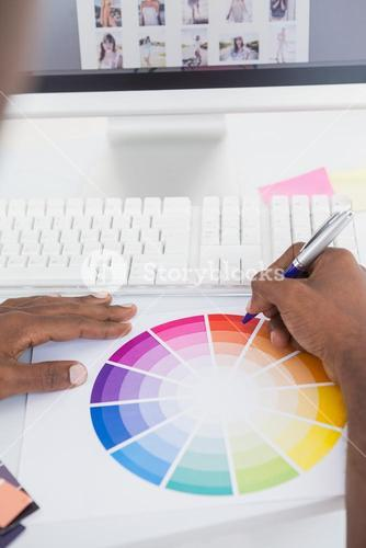 Businessman pointing with a pen on colour wheel