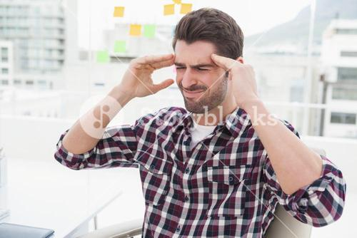 Businessman sitting with severe headache