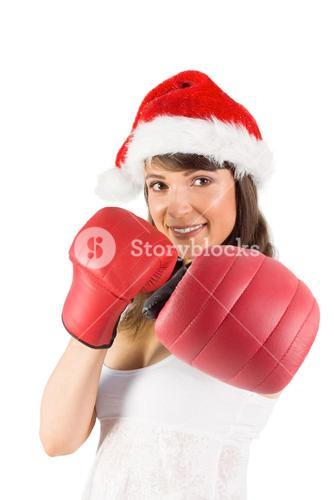 Festive brunette punching with boxing gloves