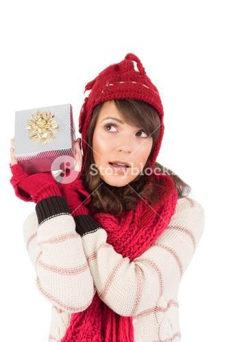 Young woman shaking her gift in order to guess what it is