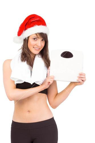 Festive fit brunette holding weighing scales