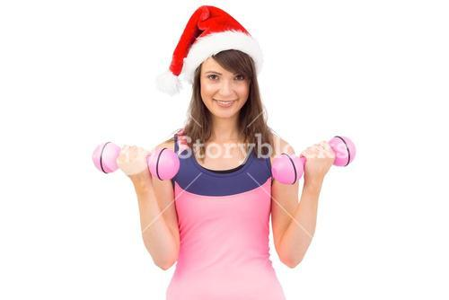 Woman in santa hat holding hand weight