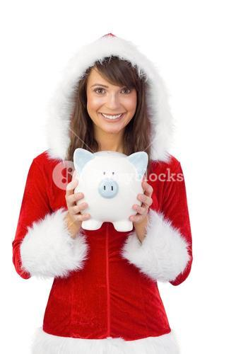Smiling brunette in santa claus holding a piggy bank