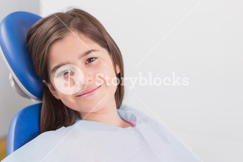 Smiling young patient sitting in dentists chair