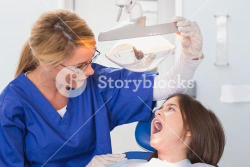 Pediatric dentist examining with a light her young patient