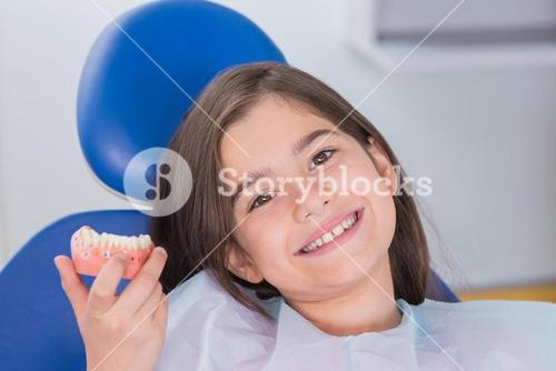 Portrait of a smiling young patient showing model
