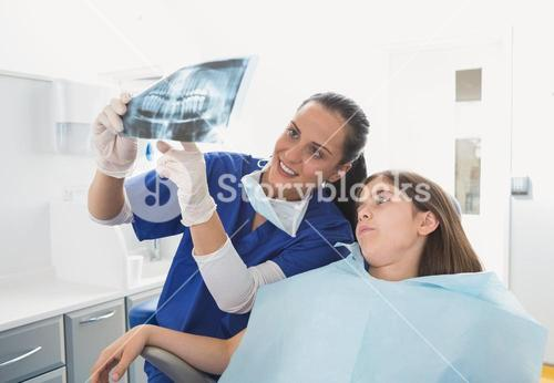 Pediatric dentist explaining to young patient the x-ray