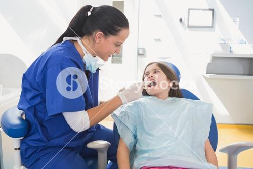 Pediatric dentist examining her young patient