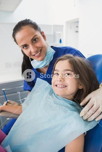 Smiling pediatric dentist with a cute young patient
