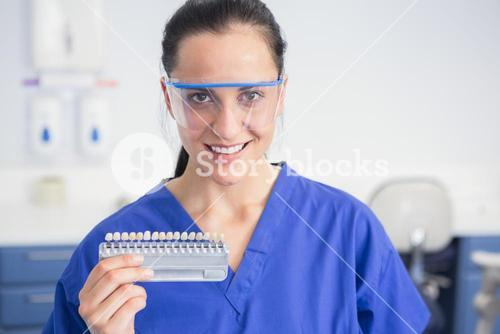 Smiling dentist with safety glasses holding teeth whitening