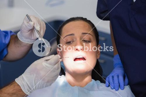 Dentist and nurse examining a scared patient