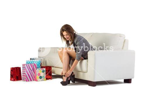 Cute woman sitting on couch taking off her shoes
