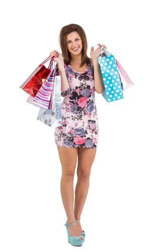 Smiling brunette in floral dress holding shopping bags