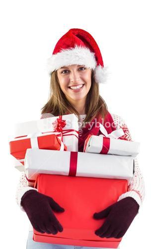 Festive brunette with santa hat holding many gifts