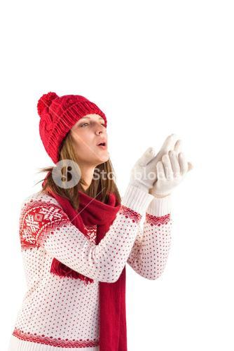 Woman in warm clothing blowing over hands