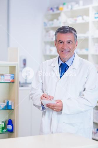 Pharmacist with grey hair writing down notes