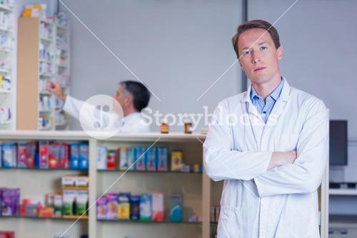 Unsmiling pharmacist standing with arms crossed