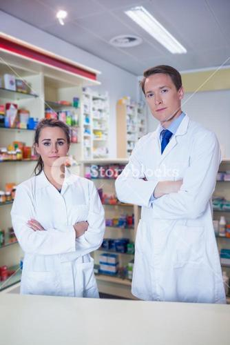 Pharmacist and his trainee standing with arms crossed