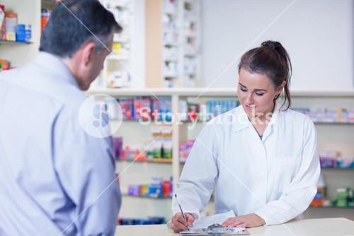 Trainee writing prescription in front of a customer