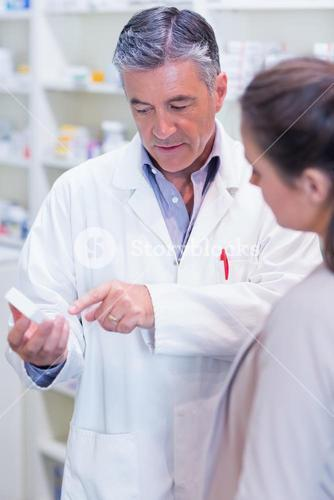 Pharmacist speaking with cheerful young customer