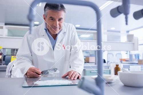 Smiling biochemist preparing some medicine