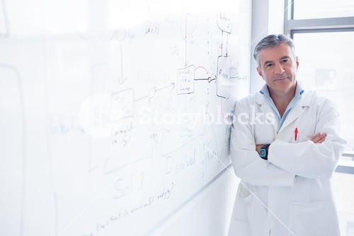 Smiling scientist leaning against the whiteboard