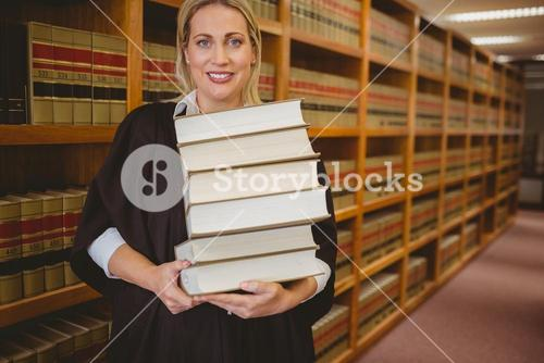 Smiling lawyer holding heavy pile of books standing