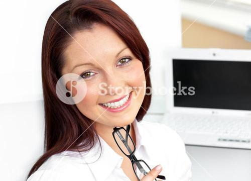 Charming businesswoman sitting in her office holding glasses