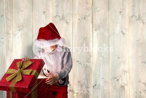 Composite image of festive boy opening gift