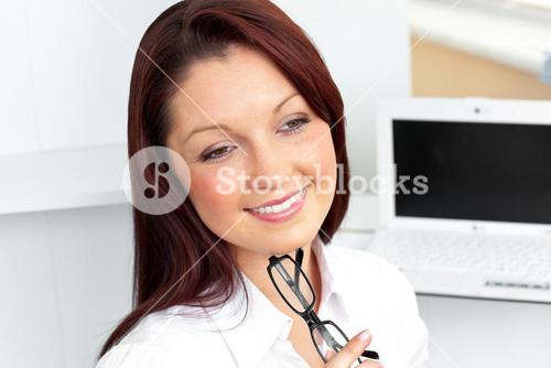 Confident businesswoman sitting in her office holding glasses