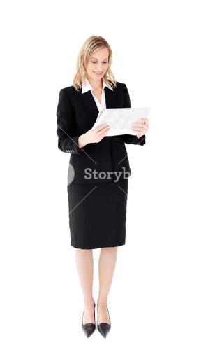 Selfassured businesswoman reading a newspaper