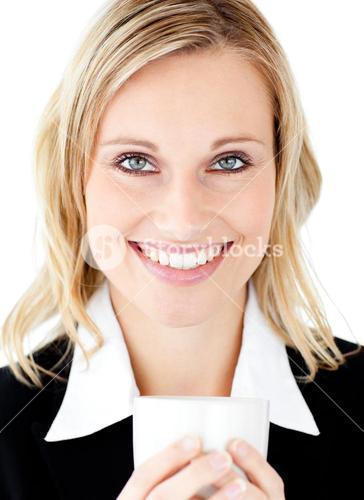 Radiant businesswoman holding a cup smiling at the camera
