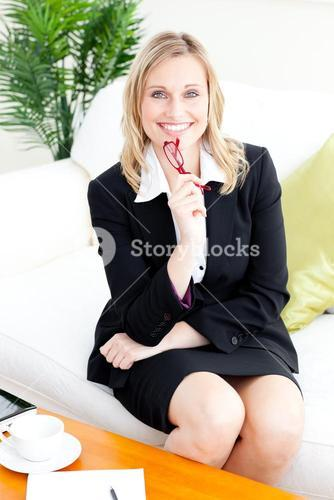 Selfassured businesswoman smiling at the camera sitting on the sofa