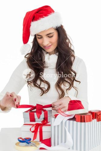 Happy brunette in santa hat packing gifts