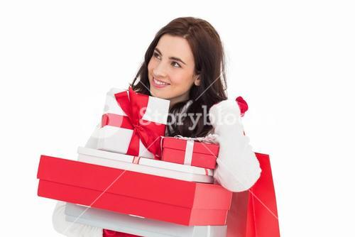 Happy brunette holding christmas gifts and shopping bags
