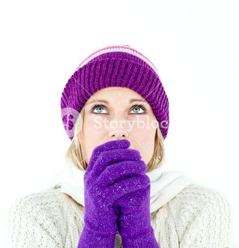 Freezing young woman wearing gloves looking upwards
