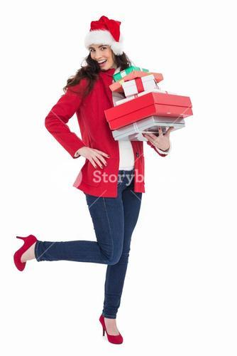 Excited brunette in red coat holding many gifts